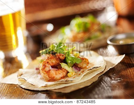 spicy shrimp avocado tacos in slanted composition