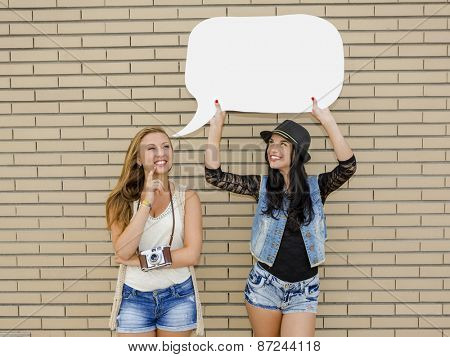 Two beautiful and young girlfriends holding a thought balloon, in front of a brick wall