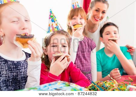Children grabbing muffins at birthday party and cake, the kids are wearing hats, balloons and paper streamers for decoration