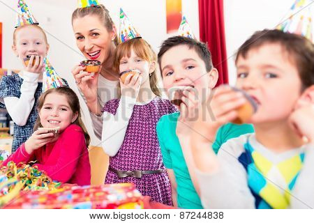 Children having cupcakes celebrating birthday on big party with all the friends and mom