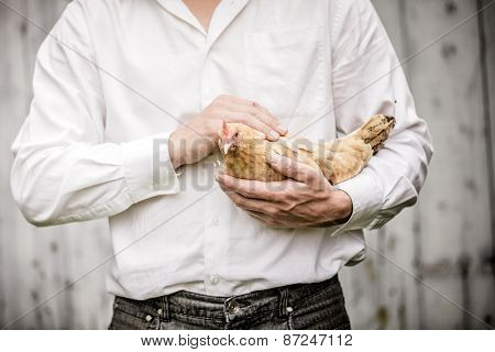 Farmer Holding A Beige Chicken