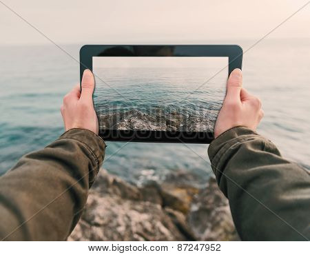 Woman Photographs Coast On Tablet Pc