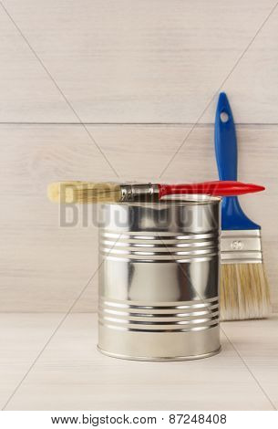 paint bucket and paintbrush  on wooden background
