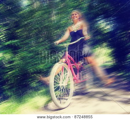 a girl riding a bike on a path in a park full of trees toned with a retro vintage instagram filter and a motion blur
