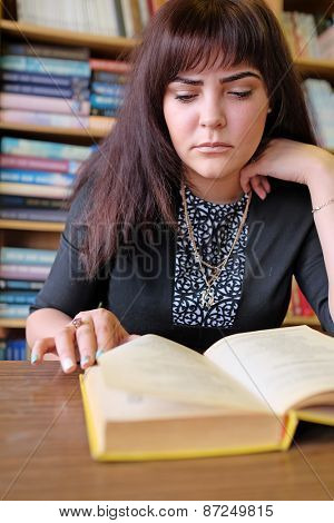 Sad female student with learning difficulties in library