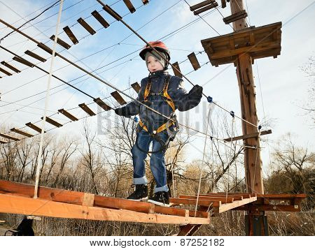 Little Boy Going On Suspension Bridge In The Equipment And Looking Down. Horizontal, Shot From Below