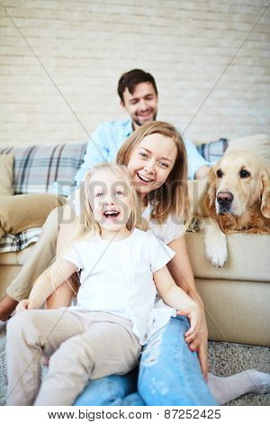 Happy female and little girl laughing with dog and young man on background