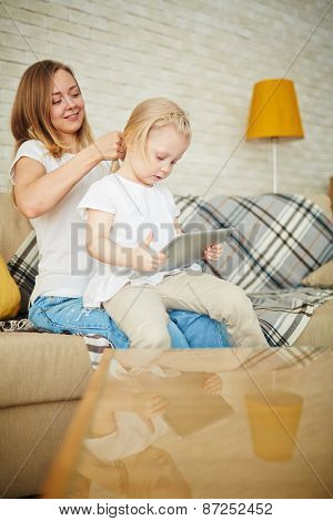 Curious girl with touchpad and her mother spending leisure at home