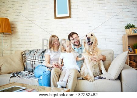 Cute little girl and her parents with dog resting on sofa at home
