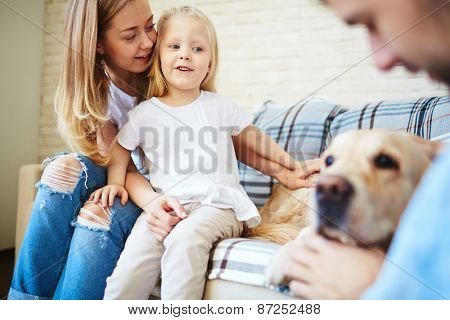 Cute little girl looking at dog with her mother near by