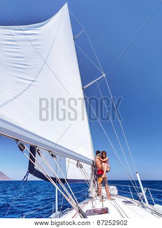 Cheerful joyful couple having fun on sailboat, enjoying wonderful summer adventure, honeymoon in sea cruise, love and happiness concept