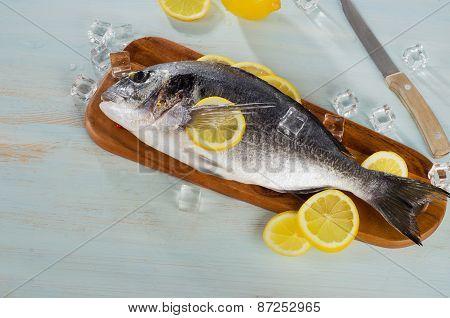 Raw Sea Bream With Lemon On  A Cutting Board.