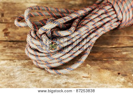 Climbing rope on wooden background
