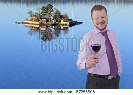 Businessman holding glass of wine with sea island in background