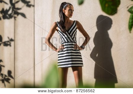 Fashion model in the striped dress on a background of textured wal