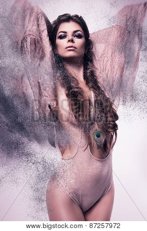 Sexy Woman With Peacock Feather In Dust