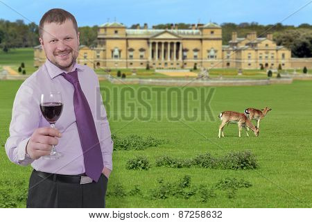 Businessman holding glass of wine with beautiful villa in background