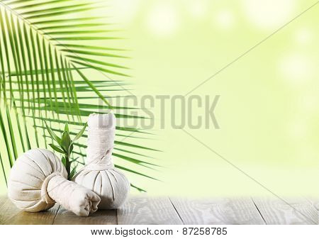Spa compress balls with green leaves on light background