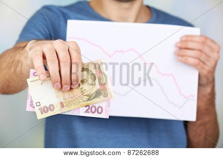 Man holding money and graph document close up