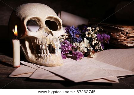 Still life with human skull and retro book on wooden table, closeup