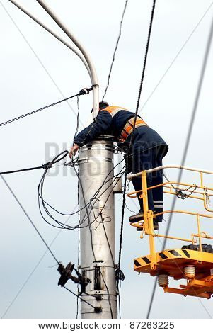 worker-electrician repairing the wires on the electric pole