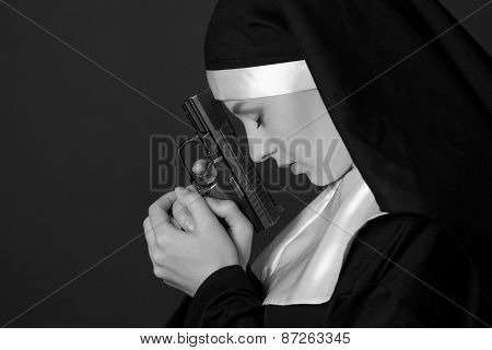 Black And White Portrait Of Woman Nun Praying With Gun