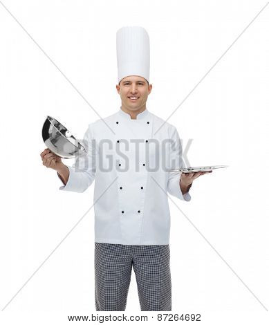 cooking, profession and people concept - happy male chef cook opening cloche cover