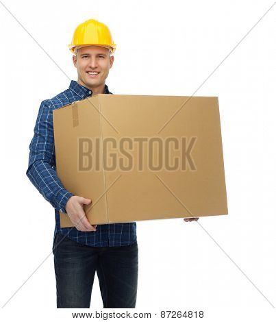 repair, construction, building, people and maintenance concept - smiling male builder or manual worker in helmet carrying big cardboard box
