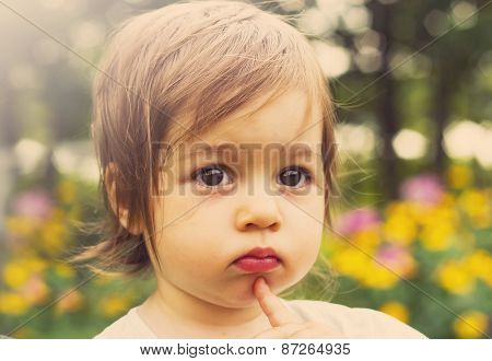 Toned portrait of Cute child thinking outdoor