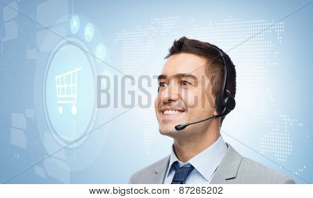 business, people, technology and customer service concept - smiling businessman in headset looking to virtual shopping trolley icon over blue background