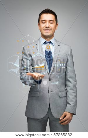 business, people, technology and statistics concept - happy businessman in suit showing virtual screens with charts over gray background