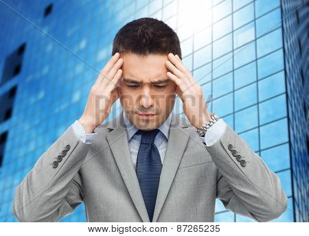 business, people, crisis and fail concept - businessman in suit having head ache over office building background