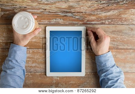 business, education, people and technology concept - close up of male hands with tablet pc computer and coffee cup on table
