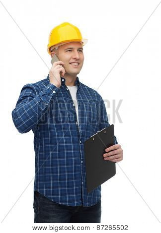 construction, building, people, technology and maintenance concept - smiling male builder or manual worker in helmet with clipboard calling on smarphone