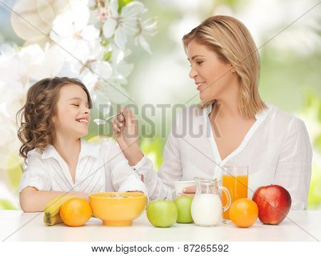 people, healthy lifestyle, family and food concept - happy mother and daughter eating healthy breakfast over green summer garden background