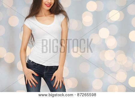 people, advertisement, holidays and t-shirt design concept - close up of smiling young woman in blank white t-shirt over lights background