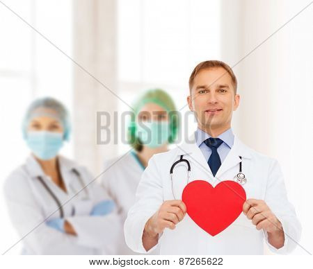 medicine, profession, charity and healthcare concept - smiling male doctor with red heart over group of medics