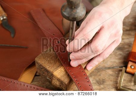 Repairing leather belt in workshop