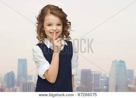 people, children, secrecy and mystery concept - happy girl showing hush gesture over city background