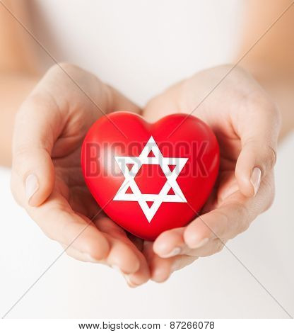 religion, christianity and charity concept - female hands holding red heart with star of david symbol
