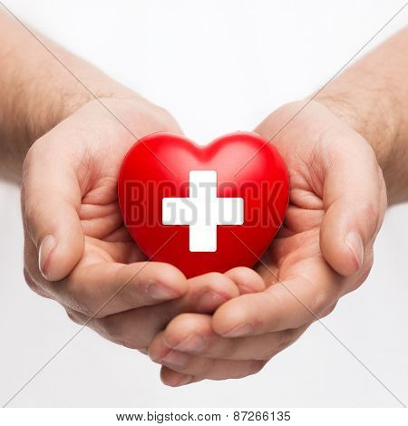 family health, charity and medicine concept - male hands holding red heart with cross sign