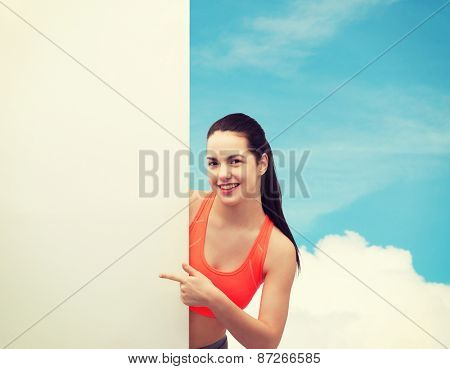 fitness and diet concept - smiling teenage girl in sportswear pointing finger to white blank board