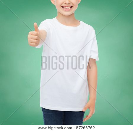 school, education, advertising, people and childhood concept - close up of smiling little boy in white blank t-shirt showing thumbs up over green chalk board background