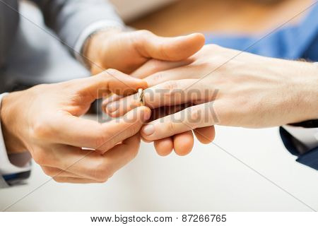 people, homosexuality, same-sex marriage and love concept - close up of happy male gay couple hands putting wedding ring on