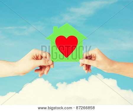 charity, real estate and family home concept - isolated picture of male and female hands holding green paper house with red heart