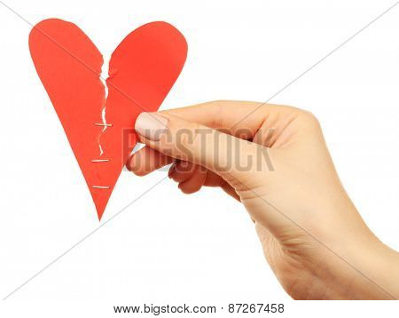 Female hand holding broken heart stitched with staples isolated on white