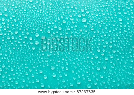 Water drops on glass on green background
