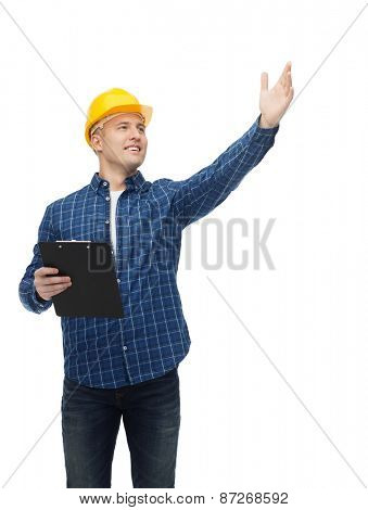 repair, construction, building, people and maintenance concept - smiling male builder or manual worker in helmet with clipboard pointing hand