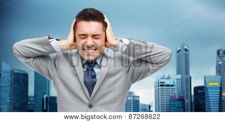 business, people, crisis and emotional pressure concept - businessman in suit covering his ears by hands over city background