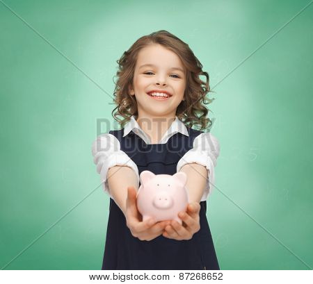 people, money, finances and savings concept - happy girl holding piggy bank on palms over green chalk board background